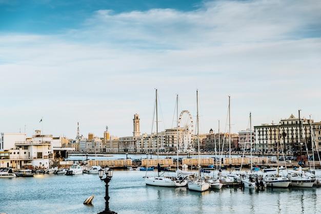 Bari, itália - 10 de março de 2019: vista do pôr do sol à beira-mar e porto turístico de bari Foto Premium