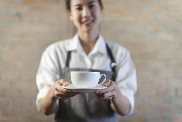 Barista asiático bonito novo na camisa agradável com o avental que serve o café quente na caneca branca na cafetaria. Foto Premium