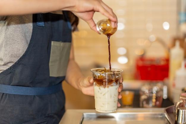 Barista derramando café para takeaway cup para fazer latte de café gelado no café. Foto Premium