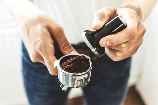 Barista do homem que mantém a calcadeira do café com o café da moagem pronto para cozinhar o café. fechar-se Foto gratuita
