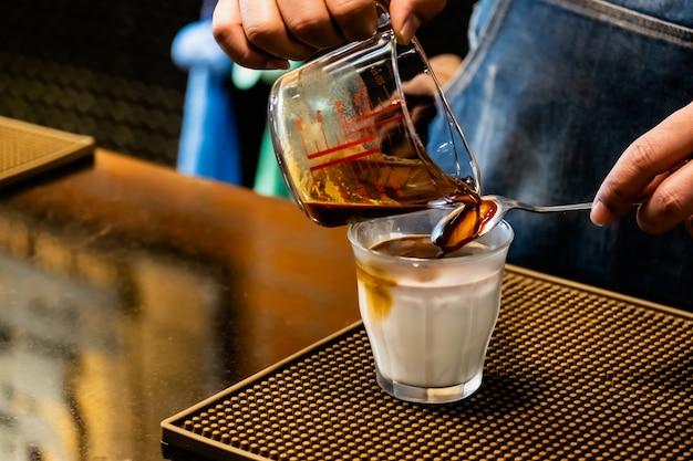 Barista fazendo café, despeje o café com gelo de leite de coco no copo Foto Premium