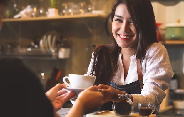 Barista fêmea asiática bonita que serve café quente ao cliente no balcão de bar Foto Premium