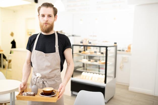 Barista jovem bonito carregando bandeja com cappuccino Foto Premium