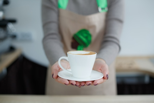 Barista no avental no café dar café fresco acabado de fazer ao cliente Foto Premium