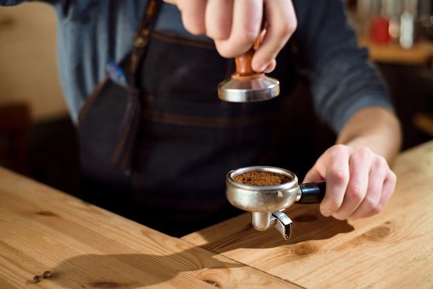 Barista pressiona café moído usando tamper em uma cafeteria Foto Premium