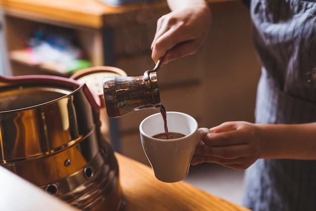 Barista profissional que serve café turco tradicional no refeitório Foto gratuita