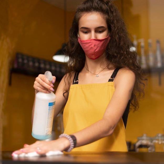 Barista usando máscara médica durante a limpeza de um café Foto gratuita