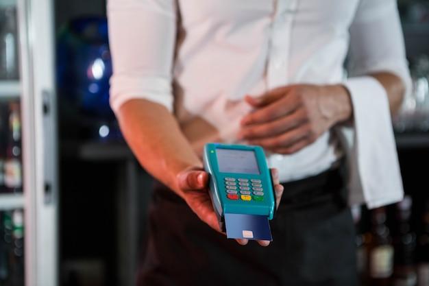 Barman, aceitar um cartão de crédito no balcão de bar em bar Foto Premium