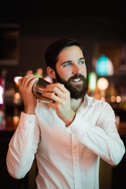 Barman agitando a coqueteleira no bar Foto gratuita