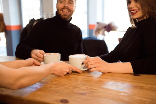 Barman amigável que serve o café do café aos clientes no interior de uma cafetaria moderna. Foto Premium