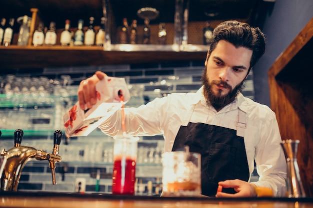 Barman bonito fazendo beber e cocktails num balcão Foto gratuita
