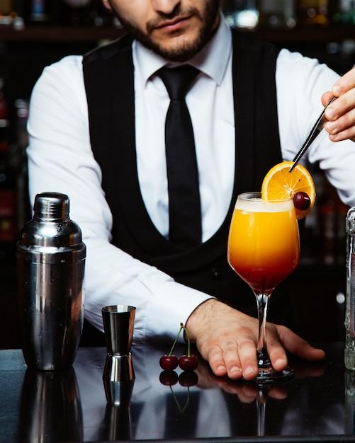 Barman coloca fatia de orage em cocktail Foto gratuita