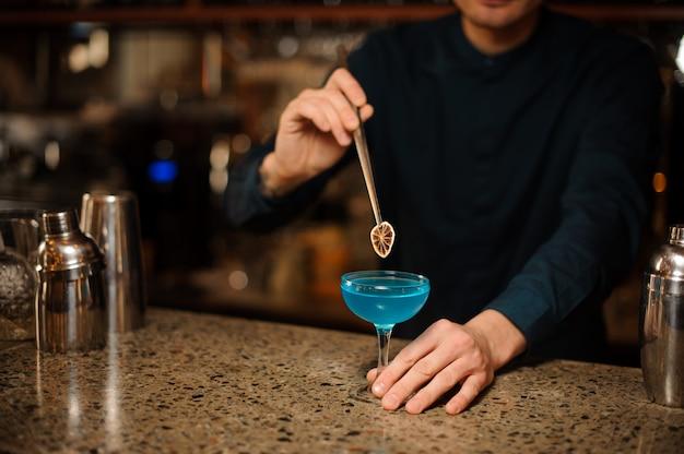 Barman, decorando um copo de coquetel de verão fresco com licor azul usando uma fatia de laranja Foto Premium