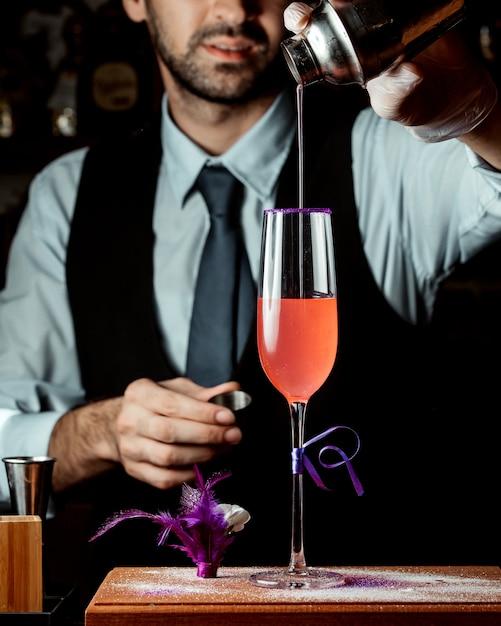 Barman derrama cocktail de coqueteleira Foto gratuita