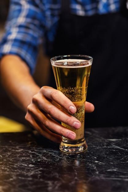 Barman, derramando a cerveja fresca no pub, barman mão na torneira de cerveja, derramando uma cerveja de pressão, cerveja da torneira, copo de enchimento com cerveja, bar. bar.restaurant.european bar. Foto Premium