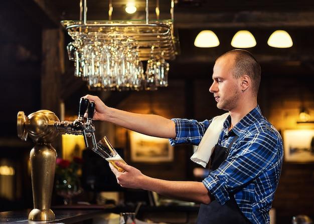 Barman, derramando a cerveja fresca no pub, barman mão na torneira de cerveja, derramando uma cerveja de pressão, cerveja da torneira, copo de enchimento com cerveja, cerveja fresca, pub. bar.restaurant.european bar. Foto Premium