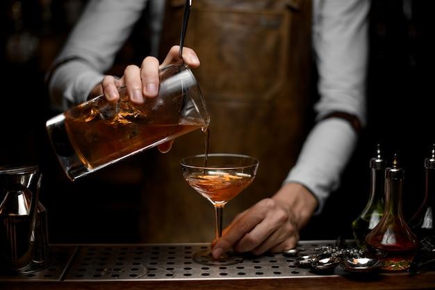 Barman, derramando álcool cocktail com um filtro Foto Premium