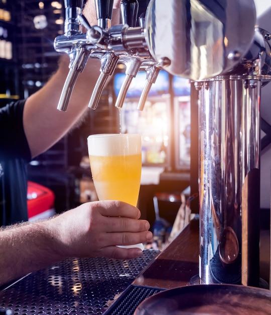 Barman, derramando cerveja em copos no bar. Foto Premium