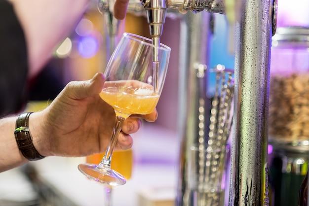 Barman derramando cerveja em um copo. Foto Premium