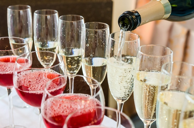 Barman, derramando champanhe no copo Foto Premium