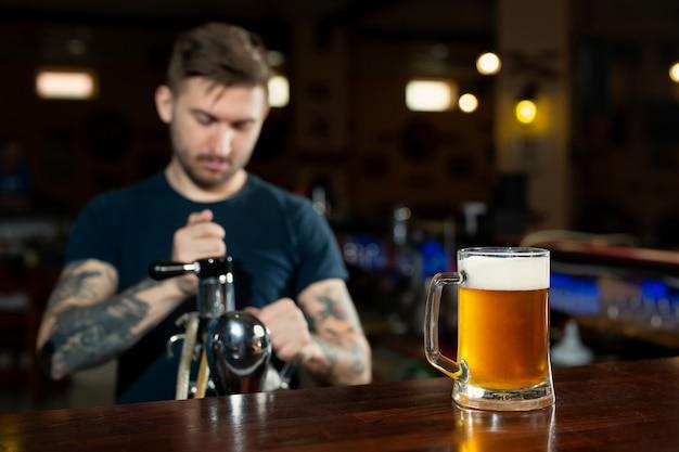 Barman, derramando da torneira cerveja fresca no copo no pub Foto Premium