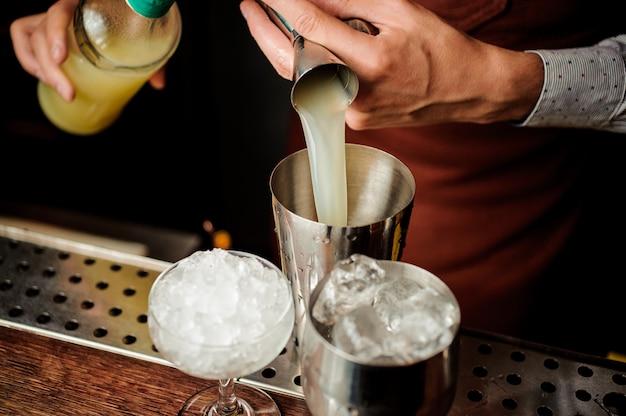 Barman, derramando um suco para fazer um coquetel alcoólico Foto Premium