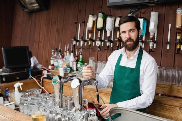Barman, enchendo, cerveja, de, barra, bomba Foto gratuita