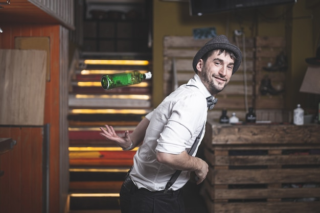 Barman especialista com chapéu e gravata borboleta jogando garrafa no ar Foto Premium
