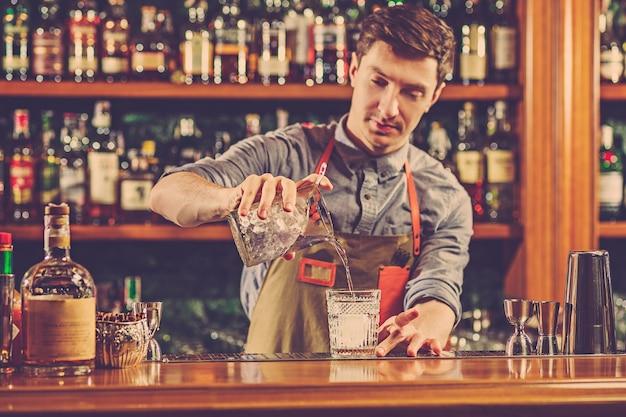 Barman especialista está fazendo coquetéis em uma boate. Foto gratuita