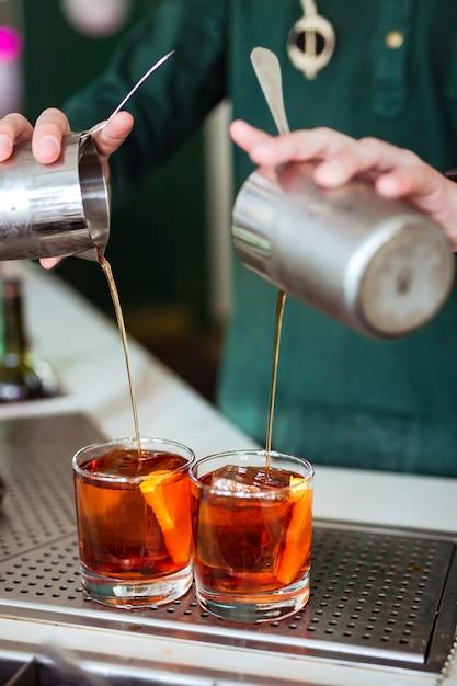 Barman fazendo um coquetel de negroni no bar: derramando uma bebida de uma coqueteleira em um copo Foto Premium