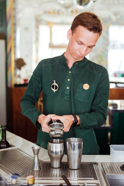 Barman fazendo um coquetel, espremendo suco em uma coqueteleira Foto Premium