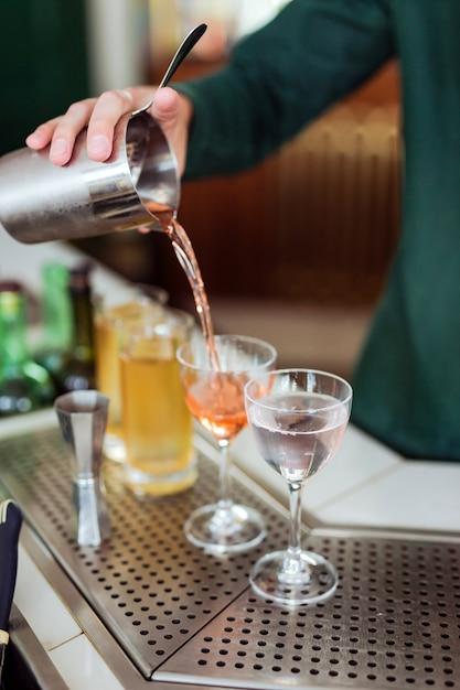 Barman fazendo um coquetel no bar: derramando uma bebida de uma coqueteleira em um copo Foto Premium