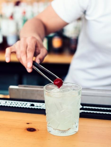 Barman masculino, adicionando a cereja em bebida Foto gratuita