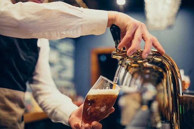 Barman masculino, derramando cerveja em um pub Foto gratuita