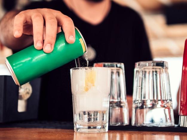 Barman masculino derramando refrigerante em coquetel Foto gratuita