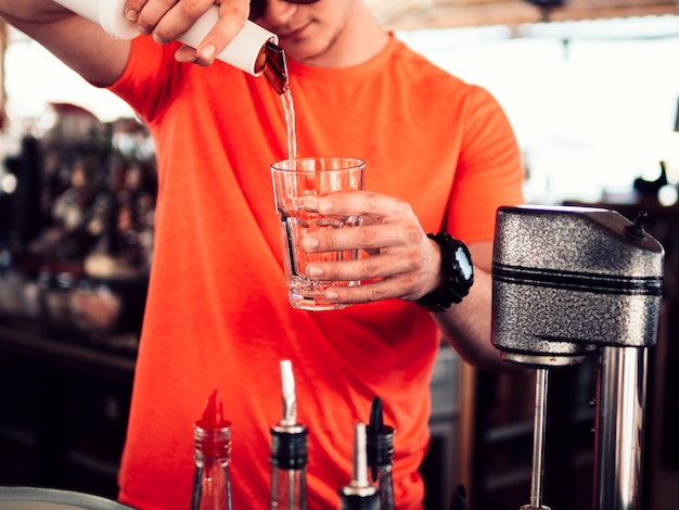 Barman masculino, enchendo de vidro com bebida desobstruída Foto gratuita