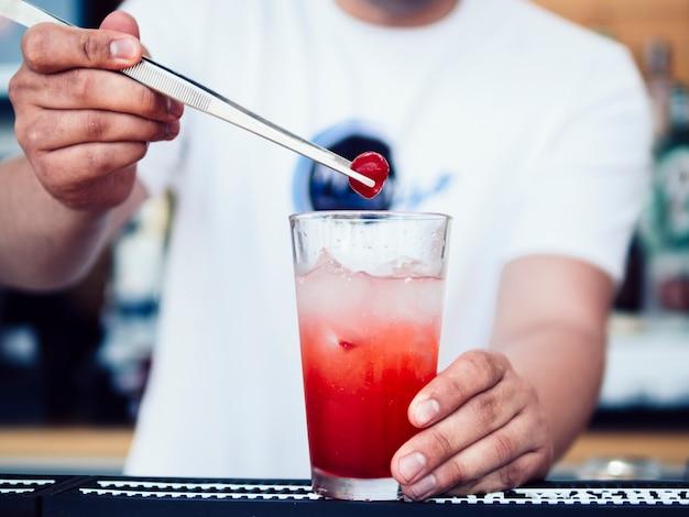 Barman masculino que decora a bebida com cereja Foto gratuita