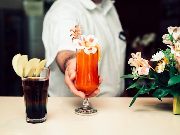 Barman masculino servindo bebida decorada colorida Foto gratuita