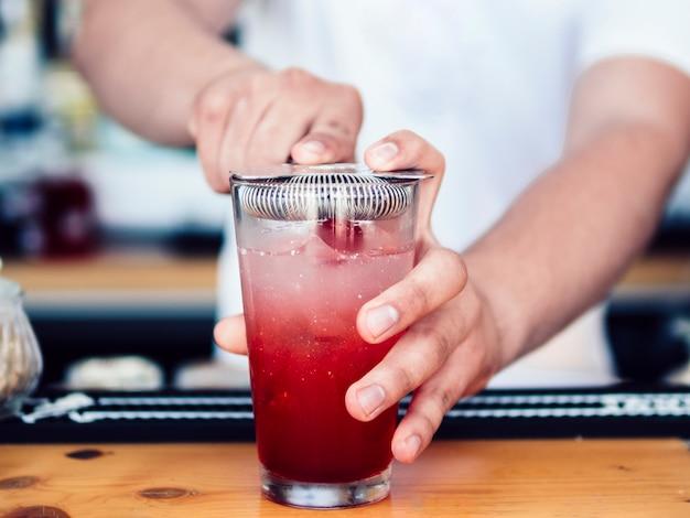 Barman masculino usando coador de coquetel Foto gratuita