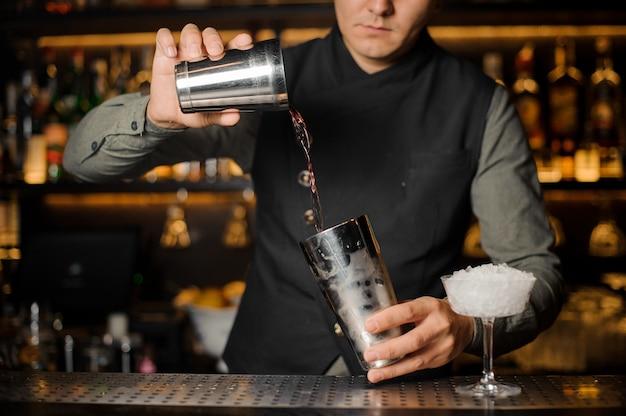 Barman mistura bebidas para fazer um cocktail Foto Premium