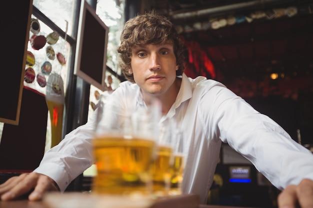 Barman, olhando para copos de cerveja Foto gratuita