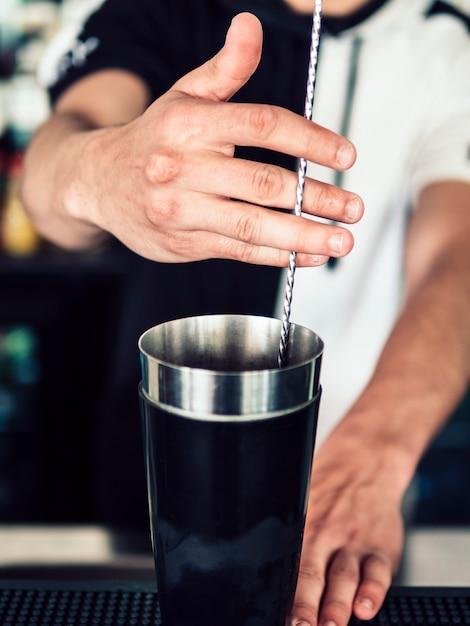 Barman sem rosto mistura de bebidas com colher Foto gratuita