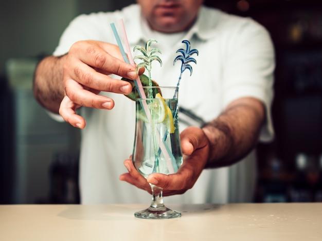 Barman sem rosto serve copo de bebida Foto gratuita