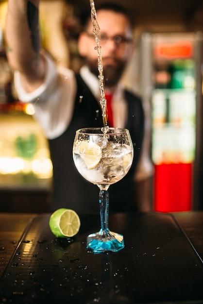 Barman servindo bebida alcoólica em copo Foto Premium