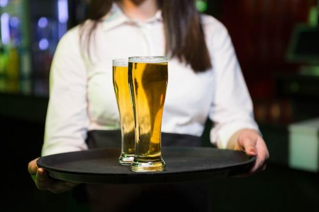 Barman, servindo dois copos de cerveja em bar Foto Premium