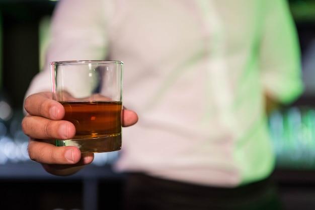 Barman, servindo um copo de uísque no bar Foto Premium