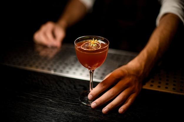Barman servindo um coquetel no copo com uma fatia de limão caramelizado Foto Premium