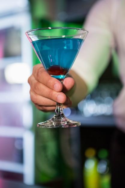 Barman, servindo um martini azul em bar Foto Premium