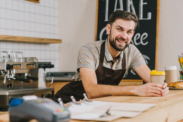Barman sorridente com bebida quente Foto gratuita