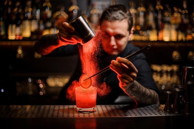 Barman tatuado adicionando especiarias em pó em um copo de coquetel com uma fatia de limão Foto Premium